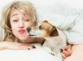 Woman waking up in bed and kissing her dog.