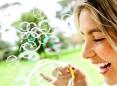 Happy woman portrait blowing soap bubbles at the park.