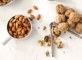 Almonds and whole walnuts being cracked.