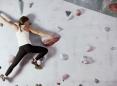 Woman scaling a climbing wall