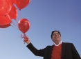Shane Lopez holding a bunch of red balloons