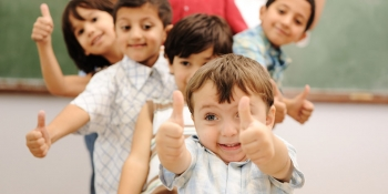 Happy children in front of a chalkboard.