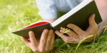 Man reading a book in the grass