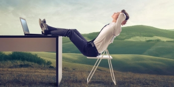 Young businessman relaxing at his desk in the middle of a green meadow.