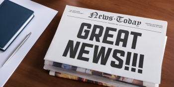 "Newspaper with headline ""Great News!"""