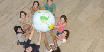 Multiracial group of people holding the Earth