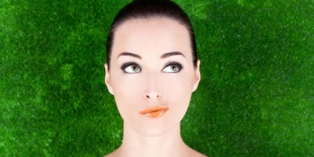 Woman looking thoughtful against green background