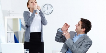 Woman sneezing at work while coworker looks at her.