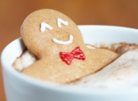 Gingerbread cookie man in a hot cup of cappuccino