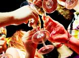 People clinking wine glasses at a party.
