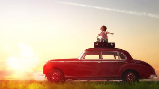 Girl sitting on top a vintage car.