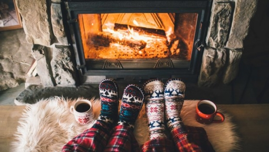 Two people warming their feet in front of a cozy fire.