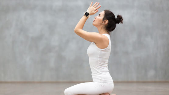 Woman doing yoga with wellness bracelet.