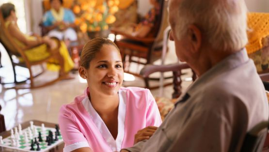 young attractive hispanic woman working as nurse takes care of a senior man on wheelchair. She talks with him then goes away to help other patients