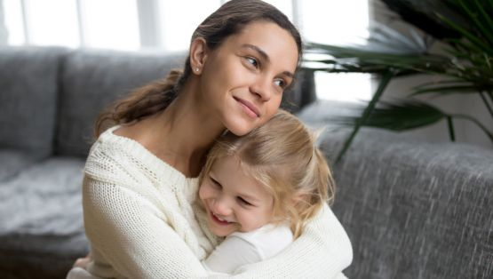 Loving grateful mother hugging cute little daughter showing love care support