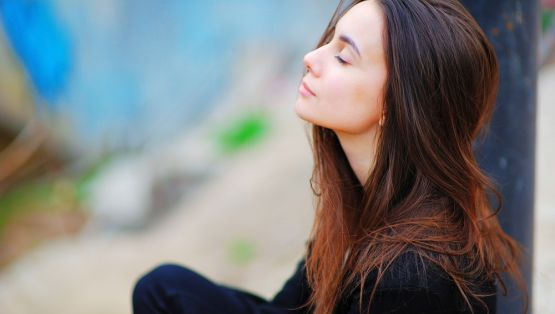 Portrait of a dreamy cute woman meditating outdoors with eyes closed, with the effect of blur, closeup.