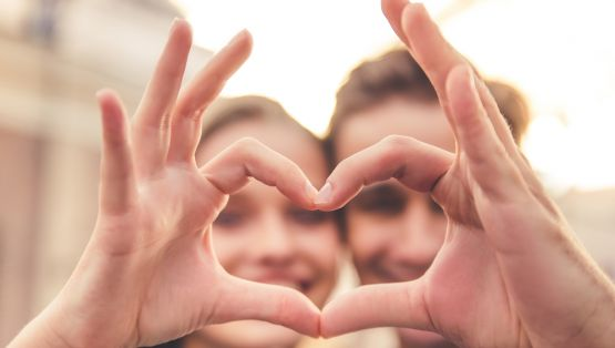 Beautiful young couple is making heart of fingers, looking through it and smiling, hands in focus, close-up