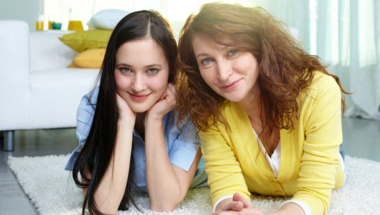 Restful mother and daughter lying on the floor at home