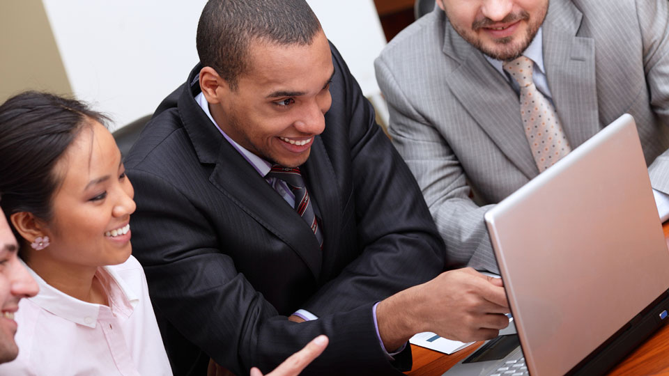 Business team looks at a computer