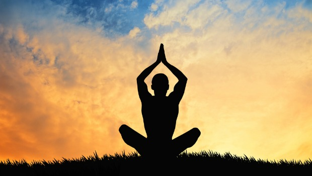 Person meditating against a sunset sky