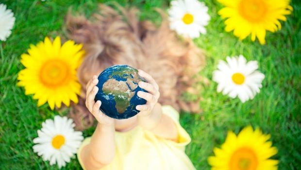 Little girl holding up a globe.