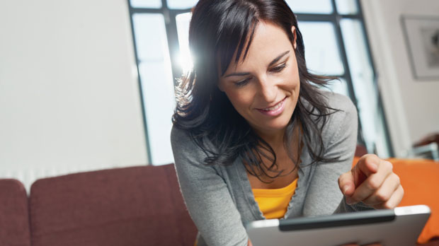 Woman looking at her tablet at home.