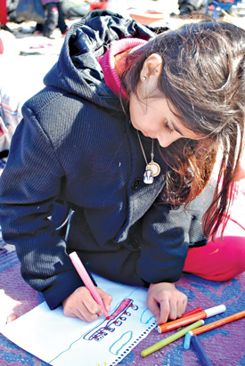 Syrian refugee girl coloring in Lesbos, Greece.
