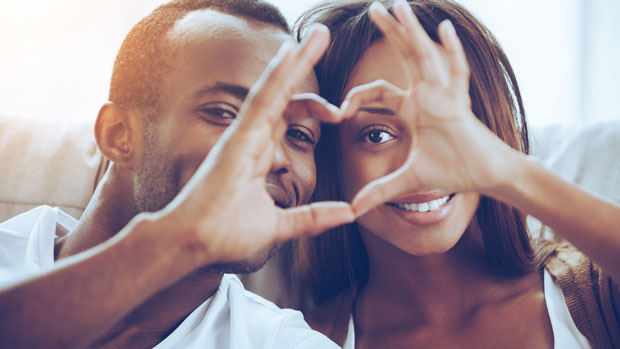 cute couple making a heart with their hands.