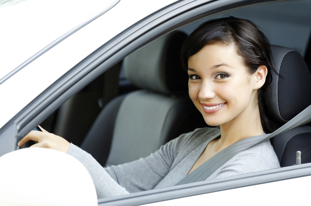 female driver in white car smiling to you.