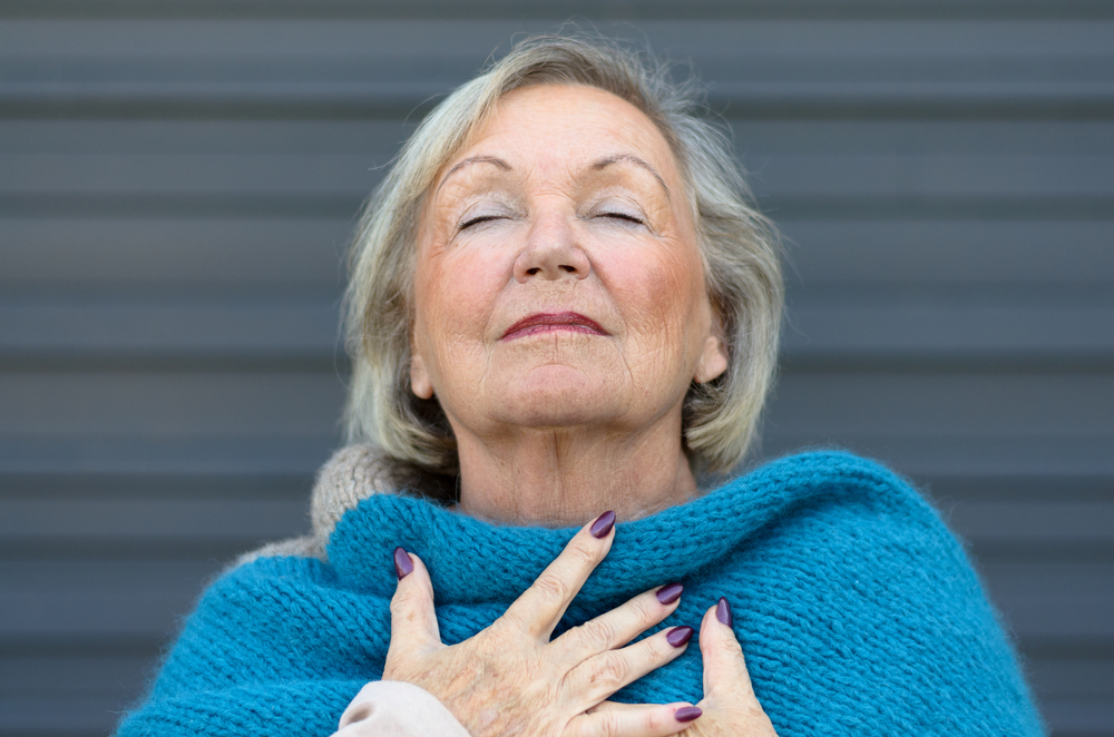 Attractive senior woman savoring the moment standing with her eyes closed and head tilted back with a serene expression