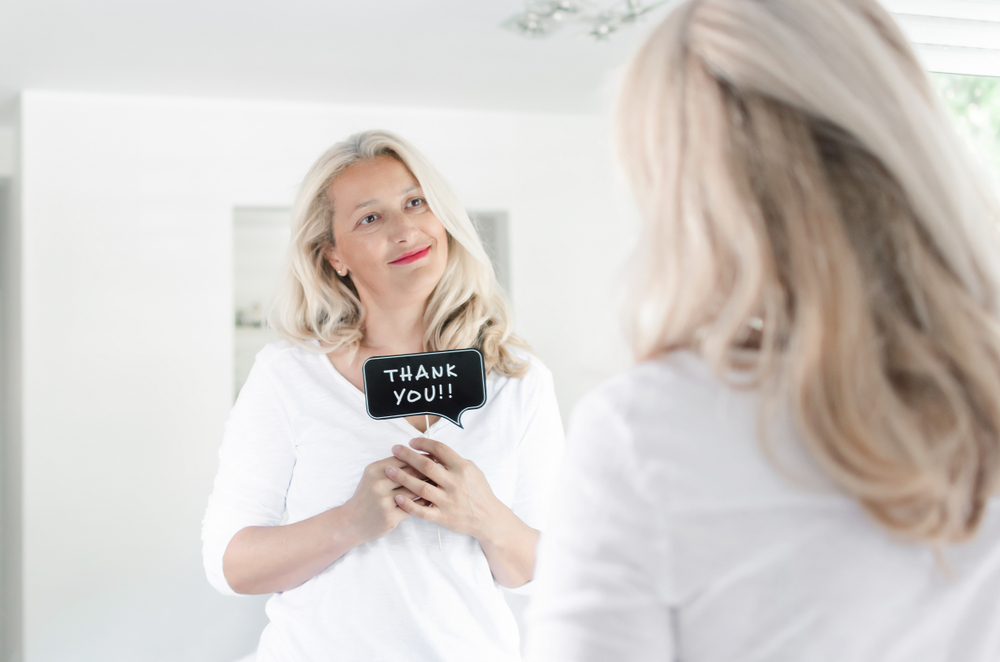 Beautiful adult woman smiling and holding photo prop in front of mirror at home