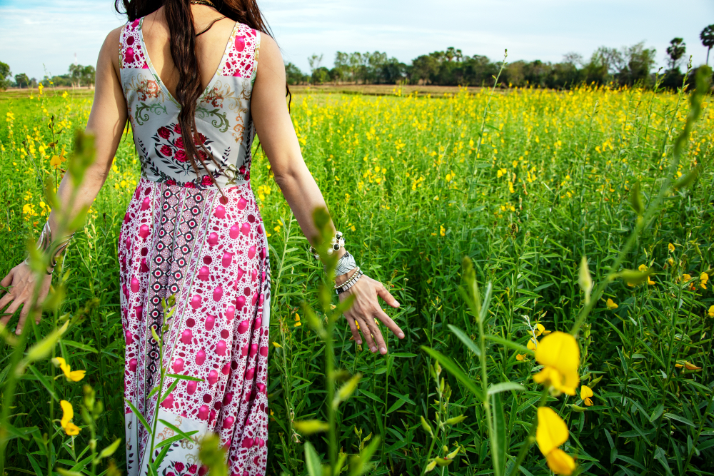 Beautiful carefree woman in fields being happy open hands outdoors on sunset in nature summer.