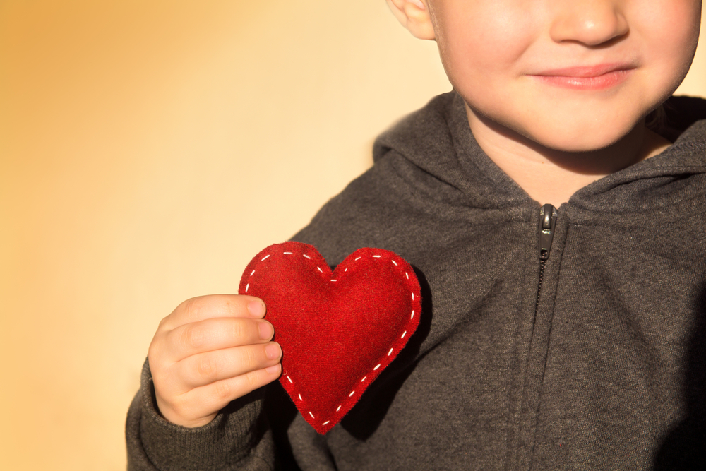 Red heart in child hands. Kindness concept, gift, hand made valentine, close up.