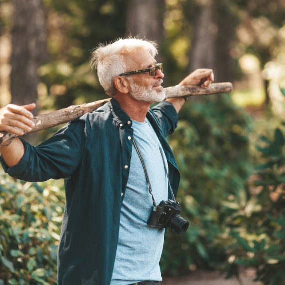 A mature bearded grandfather holds a stick on his shoulders. A pensioner man enjoys life, walking in the woods. Outdoor activities in old age.