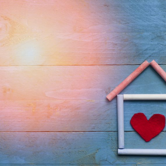House made of chalk with red heart in on blue wooden background. Sun in a corner