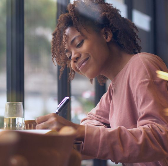 Side view of one happy young African woman writing indoor, Pretty Black college student study with laptop by the window doing homework writing letter