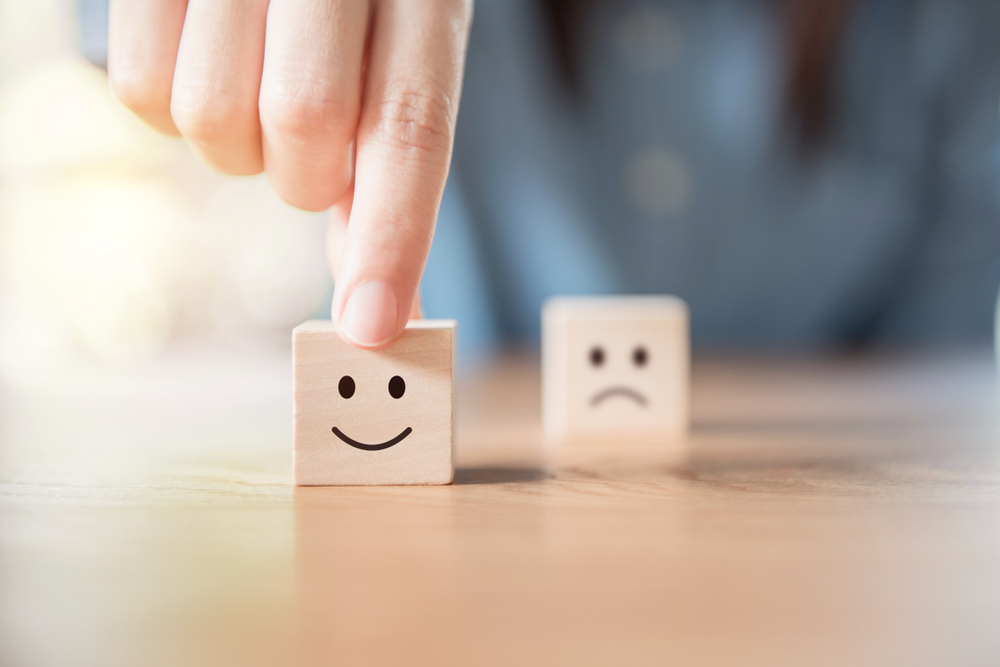 Close up customer hand choose smiley face and blurred sad face icon on wood cube, Service rating, satisfaction concept.